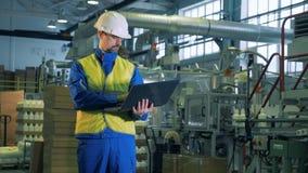 A pessoa trabalha com um portátil ao estar em uma sala da fábrica, tecnologia moderna filme