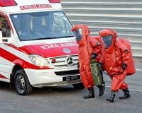 Pessoais em ternos protetores químicos durante NDP Foto de Stock