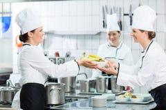 Pessoal da cozinha na cantina que prepara pratos imagem de stock royalty free