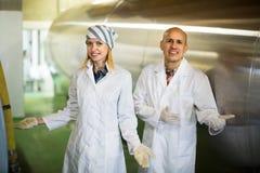 Pessoal da exploração agrícola com os reservatórios do leite na planta imagens de stock