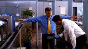 Pessoal da segurança masculino que usa o detector de metais no homem filme