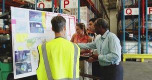 Pessoal de depósito em discussão em um painel de informações 4k vídeos de arquivo
