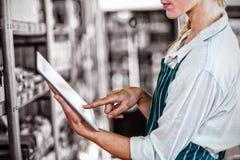 Pessoal fêmea que usa a tabuleta digital no supermercado foto de stock royalty free