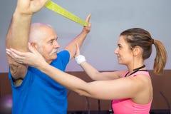 Pessoal-instrutor que dá certo com treinamento do homem de faixa elástica foto de stock royalty free