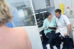 Pessoal médico da radiologia no ombro despido dos pacientes da discussão no primeiro plano imagem de stock