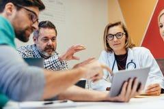 Pessoal médico durante a instrução da manhã na sala de reuniões fotografia de stock