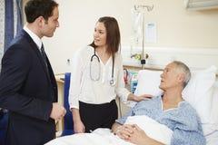 Pessoal médico em círculos que examina o paciente masculino superior Imagens de Stock