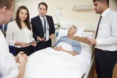 Pessoal médico nos círculos que estão pela cama do paciente masculino imagem de stock royalty free