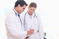 Pessoal médico novo que trabalha no registro do paciente Fotografia de Stock Royalty Free