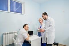 Pessoal médico que discute sobre relatórios médicos usando o PC do portátil e da tabuleta Profissionais dos cuidados médicos que  imagens de stock royalty free