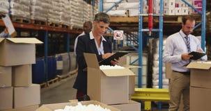 Pessoal num armazém que prepare uma entrega de 4.000 video estoque