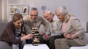 Pessoas adultas ativas que jogam o jogo do bloco, passando o tempo na atmosfera amigável video estoque