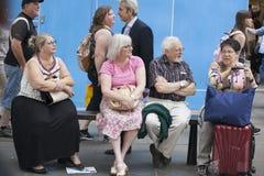 Pessoas adultas nos vidros que sentam-se no banco na rua Tenha pouca ruptura Fotografia de Stock