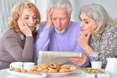 Pessoas adultas que comem o café da manhã e que leem um jornal Fotos de Stock Royalty Free