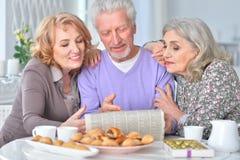 Pessoas adultas que comem o café da manhã e que leem um jornal Foto de Stock