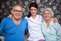 Pessoas adultas satisfeitas de sorriso com enfermeira fotografia de stock royalty free