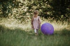 Pessoas de 2-5 anos à moda do bebê que guardam o balão grande que veste o vestido cor-de-rosa na moda no prado playful fotografia de stock royalty free