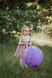 Pessoas de 2-5 anos ? moda do beb? que guardam o bal?o grande que veste o vestido cor-de-rosa na moda no prado playful fotografia de stock