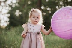 Pessoas de 2-5 anos ? moda do beb? que guardam o bal?o grande que veste o vestido cor-de-rosa na moda no prado playful fotos de stock royalty free