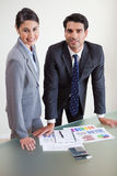 Pessoas de sorriso das vendas que estudam seus resultados Fotografia de Stock Royalty Free