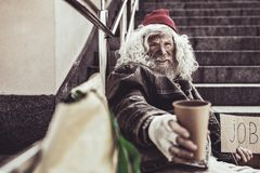 Pessoas idosas desabrigadas que oferecem a seu tampão de quem ele que realiza em uma mão para a esmola foto de stock