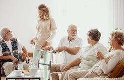 Pessoas idosas que passam o tempo na sala comum da casa do cuidado imagens de stock