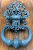 Pessoas que bate à porta ornamentados na porta de madeira imagens de stock royalty free