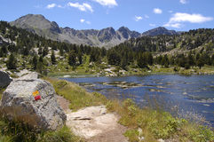 Pessons Lakes. In Andorra with the yellow and red route marking on a stone Royalty Free Stock Photo