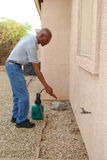 Pest Control. Male senior citizen using a do-it-yourself pest control kit to spray the side of his house in the backyard Royalty Free Stock Photography