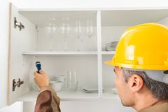 Pest control worker checking shelf. Pest Control Worker With Flashlight Checking Kitchen Shelf Royalty Free Stock Photography