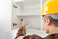 Pest control worker checking shelf Stock Photography