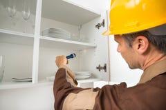 Pest control worker checking shelf. Pest Control Worker With Flashlight Checking Kitchen Shelf Stock Photos