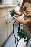 Pest control worker holding pesticides sprayer. Close-up Of Pest Control Worker Hand Holding Sprayer For Spraying Pesticides On Cabinet Stock Photos