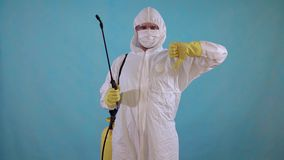 Pest control worker in overalls with spray showing thumbs down