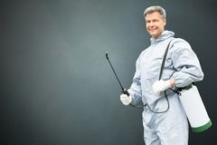 Pest Control Worker In Protective Workwear. With Pesticides Sprayer Over Gray Background Royalty Free Stock Image