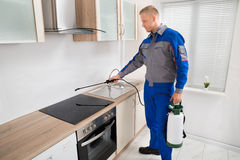 Pest Control Worker Spraying Pesticide On Induction Hob. Young Male Pest Control Worker Spraying Pesticide On Induction Hob In Kitchen royalty free stock photography