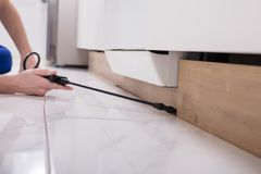 Pest Control Worker Spraying Pesticide On Wooden Cabinet. Close-up Of A Pest Control Worker`s Hand Spraying Pesticide On Wooden Cabinet Stock Photo