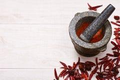Pestello con il mortaio, circondato dai peperoni secchi del habanero e del peperoncino rosso Fotografia Stock