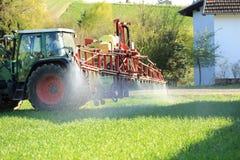 Pesticida de rociadura del tractor cerca de casas Imagenes de archivo