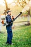 pesticida que cultiva un huerto y de rociadura del trabajador de granja imágenes de archivo libres de regalías