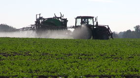 Pesticidas de rociadura de los fertilizantes del tractor en campo de la rabina almacen de video