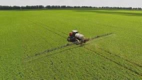Pesticidas de rociadura del tractor en campo de la soja con el rociador en la primavera Tiroteo aéreo de Quadcopter almacen de video