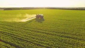 Pesticidas de rociadura del tractor en campo de la soja con el rociador en la primavera Tiroteo aéreo de Quadcopter almacen de metraje de vídeo