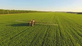 Pesticidas de rociadura del tractor en campo de la soja con el rociador en la primavera Tiroteo aéreo de Quadcopter metrajes
