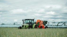 Pesticidas de rociadura del tractor en campo de trigo con el rociador en la primavera almacen de video
