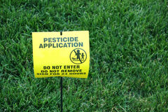 Pesticide Application. A yellow sign on the grass, warning people to stay away, because pesticide has been applied stock image