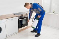 Pesticide de pulvérisation d'homme dans la chambre de cuisine photographie stock