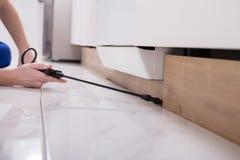 Pesticide de pulvérisation de travailleur de lutte contre les parasites sur le Cabinet en bois photo stock