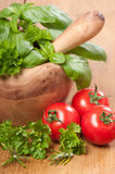 Pestle & Mortar With Herbs. And tomatoes on rustic wooden table Stock Photo