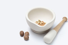 Pestle and Mortar with Spices. A stoneware pestle and mortar with nutmeg, cardamon and mustard seeds.  Horizontall (landscape) orientation with copy space to Stock Photos